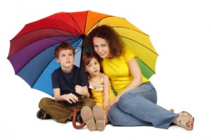 mother, daughter and son with big multicolored umbrella sitting
